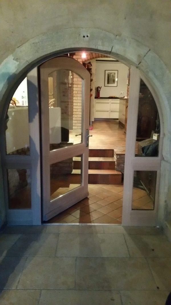 Porte latérale en chêne avec 2 parties fixes et un ouvrant central, partie haute en plein cintre